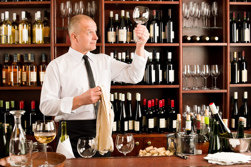 Wine bar waiter clean glass in restaurant
